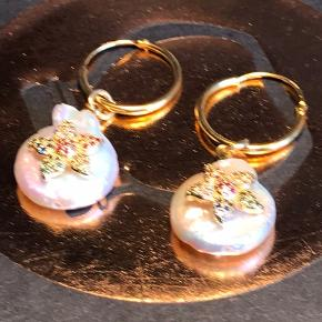 Smukke forgyldte kvalitets sterlingsølv Creol med håndlavet ferskvandsperle med farvede zirkoner. Øreringen måler 18 mm. Perlen kan tages af og øreringen bruges alene. Smukke sammen med smykker fra Maanesten, Anni Lu, Jane kønig og Stine A. De sælges enkeltvis, og det er meget få tilbage.