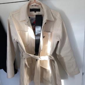 Sælger denne lækre jakke fra meotine. Kun brugt et par få gange.  Jakken kommer med både et beige bindebånd og et sort bælte.  Nypris var 1500  Byd