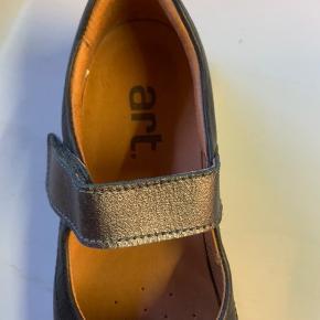 Brand: Art (skoen hedder Rambla) Farve: Blåsort Gode flade og sporty sko fra spanske ART.  Denne model har praktisk rem som blot lukkes med velcro. Virkelig lette og behagelige sko. Nypris 800kr.   Jeg har brugt dem mav 3-4 gange.   Materiale: læder. Indersål: microfiber. Bund/hæl: gummi.  -------------------------------------------  ART er sko og støvler med attitude, funky farver samt udsøgt kvalitet og komfort.   ART er et spansk skomærke inspireret af kunst, arkitektur, mode og mennesker.   ART er vegetabilsk garvet skind, genbrugskork, genbrugspap til skokasser og naturgummi.