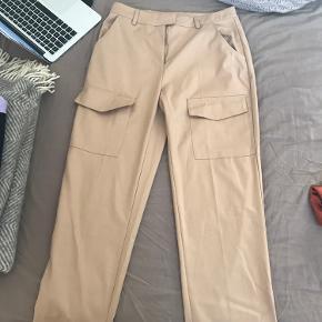 Løse bukser fra Na-kd. Størrelse 38 Aldrig brugt. Jeg synes de er super fede, men jeg får dem ikke brugt   Kan bruges med bælte