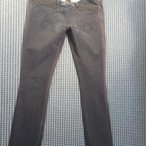 Lækre bukser fra Robins Jeans Størrelse: 28 (svarer til str. 38) Oprindelig købspris: 2.899 kr.  Super lækre bukser fra Robins jeans med små nitter bagpå. De er grå og farven ses bedst på det billede hvor de er foldet sammen. Solen har affarvet dem i siden, se eks. på et af billederne, det er ikke noget man ser når de er på, men derfor den lave pris.  Kan sendes med Dao for 40 kr. eller afhentes i Århus C.