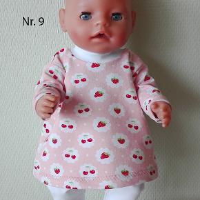 Lyserød kjole med kirsebær og jordbær og hvide leggings. Syet i økologisk bomuld.