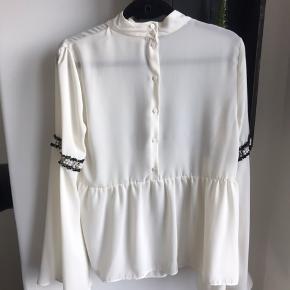 Let gennemsigtig cremefarvet skjorte med brede ærmer, knapper i ryggen og detaljer på ærmerne. Brugt få gange.  Køber betaler fragt eller afhentes hos mig på Amager