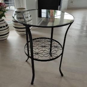 Varetype: Bord  Farve: Sort   Bordet har en glas plade foroven. Neden under er der en hylde, det er den blomstre mønstret. Glas pladen har to ridser og nogle små (billede 3) Køberen henter selv bordet.