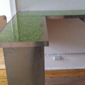 Disk / bardisk / receptions disk Jeg har brugt den som receptionsdisk i min forretning.  Materiale : aluminium og glasplader, samt aftageligt ben som kan justeres i højden. Diskens ene side monteres evt i væg, vinklen der sættes på er aftagelig, hvis man pludselig har brug for plads. Glas pladerne kan tages op hvis man vil skifte design på bordet, på fotos ses grønt materiale der er lagt i. Den har en skuffe med lås.  Mål : længde mod væg 1.30 Bredde: 40 cm stykket ud i rummet : 90 cm (130 når den er monteret på delen mod væg) Disken er designet af en snedker, jeg gav 7000,- incl arbejdsløn Giv et bud! ALT har interesse  Ring / sms 24424402.