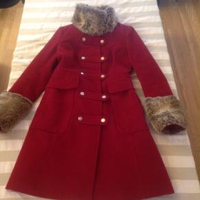 Gorgeous rich red coat in a size 38 EU by Karen Millen.  I think it fits a little small for 38 EU.  Deep pockets and fur around the collar and hands. I paid over 2000kr   I hardly used it. It was my special occasion coat.  Sadly, it's never used which is why I'm selling it.  It's really stunning.