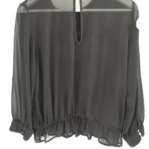 Sort bluse fra Zara med trekvart ærmer og brodering. Blusen har gennemsigtige ærmer og ryg. Derudover har den elastik i bunden og kan åbnes med en knap i nakken.