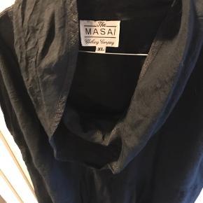 Flot kjole med spændende sort stof med kobbertråd. Lomme højre front og elastik i søm i bunden af kjolen