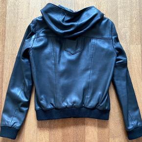 """Virkelig fed """"Be the logo"""" læderjakke (style Hanson Hood Leather Jacket, female) med hætte, lynlås og ribkant - virkelig virkelig virkelig cool. Den er i perfekt stand, fra ikke ryger-hjem og minimal brugt, har stort set kun hængt i skabet."""