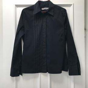 Elegant skjorte i bomuldskvalitet med lidt spandex, der giver et rigtig godt fit. Måler 49 cm over brystet og 62 cm i længden. Kontrasttråden i højre side fremstår hvid på billederne, men er reelt lys gylden.   Sælges meget billigt, så prisen er endelig.