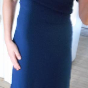 Beskrivelse Flot kjole med flæser foran og nederst på kjolen. Kjolen har været brugt to gange. Farven er mørkeblå. En flot kjole til hverdag og til fest. Er inderforret i satin inderst. Kjolen er mærket str M, men svarer til en Small. Med skjult lynlås i siden. Brystvidde: 84 cm, Længde: 107 cm. Sendes med DAO pris inkl porto.