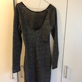 Kjole fra H&M. Sort med sølv glitter. Brugt 1 gang og er desværre blevet for lille. Den er lidt åben på ryggen og sider super pænt. Str. 34