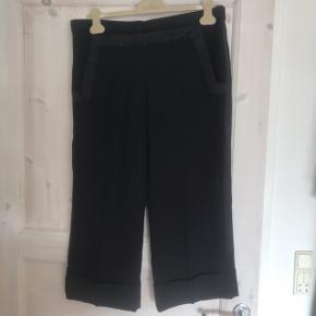 Trekvartlange suitbukser med vidde i benene og detaljer både foran, bagpå og i buksebenene. Er str. 40, men en lille smule små i størrelsen.  Befinder sig i Roskilde, men kan sende med DAO eller afhentes i Rødovre eller på Teglholmen i København efter aftale ☀️