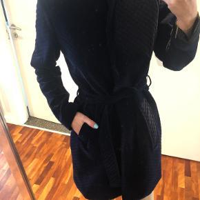 Kviltet blazer/cardigan i blå velour Foret med satin Kort krave Knaplukning Bælte i taljen  Skrålommer  Aldrig brugt