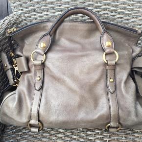 Miu Miu-taske, elsket i årevis, og det kan ses. Slid på kanter og ved hank. Aftagelig skulderrem. Mål 36x17x23. Fed gråligbrun farve. Dustbag medfølger.