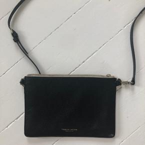 Den populære lille taske fra Tiger  Det kan ses på den hvide side at den er brugt men ikke så meget på den sorte. Remmen er blå. Fin detalje. Det ses også på guldhardware at den er brugt. Det gjorde det neget hurtigt