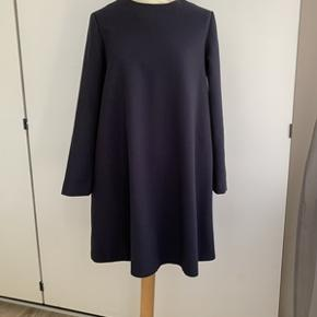 Flot klassisk mørkeblå kjole i A-form fra COS str. 38. Kjolen har lynlås i ryggen og fremstår i særdeles fin stand. Fra ikke ryger hjem. Brystomkreds 100 cm og længde 89 cm. Materiale; 63% polyester, 33% viskose og 4% elastan.