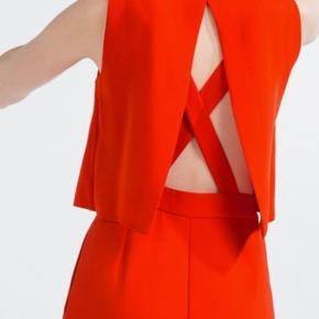 Koral/rød buksedragt med smukkeste ryg detalje.