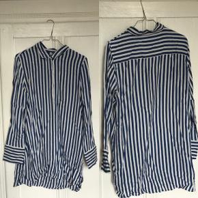 Stribet skjorte i hvid og blå. Oplagt til sommeraftener. Kan både bruges til jeans og som en kort kjole - afhængig af ens højde.  Er lidt lille i størrelsen, især hvis man har en stor barm.