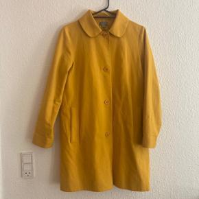 Fin solgul overgangsfrakke, som jeg desværre ikke får brugt. Den er dejlig at have på, og af kraftigt bomuld.