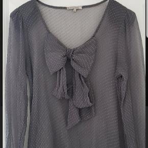 🌸 SCARLETT ROOS. Fransk tøjdesigner I transparent grå silke.  Med stor sløjfe effekt foran.  Små skulderpuder. Bindebånd ved ærmer. Str er mærket: 2.  = M/L