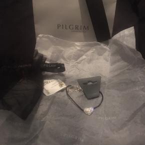 """Det smukkeste, tynde læder armbånd med glimtende sølv hjerte vedhæng fra Pilgrim. Jeg fik det i gave tilbage i 2013 men fik det aldrig byttet, da det ikke lige var mig alligevel, derfor sælges det videre da det er syndt det bare ligger i gemmeren.   Som man kan se er det købt i Magasin, standen er """"ny, med prismærke"""" da ALT medfølger, som vist på billederne; indpakning, gavepose, bytte-mærket, derfor altså ALDRIG blevet taget i brug 😊✨  Prisen kan jeg ikke se på byttemærket men tror det har ligget omkring de 300-350 kr.  Hvis det skal sendes, betaler køber fragt.  Mvh Betina Thy"""