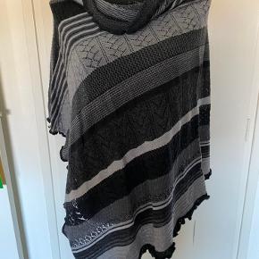Den fedeste poncho i sort/grå farver.  100% ren merino uld.