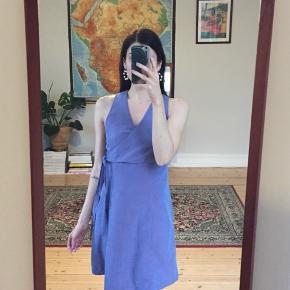 Kjole af eget design med wrap-effekt på øverste del. Blå/lilla materiale. Lynlås i siden. Fitter str. S.