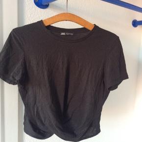 Sort crop T-shirt fra Zara. Har fin detalje foran, hvor stoffet krydser på maven.
