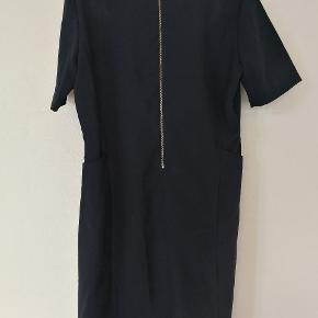 Fin faconsyet kjole. Med inderkjole. Har dyb lomme i hver side.