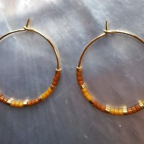 1 par medi creoler (25mm) i forgyldt messing med 24kt guldbelagt Delica Beads, matte gulbrune Delica Beads og  matte havtornsgule Delica Beads.   Stand: Helt nye. Jeg laver dem selv.   Bemærk: Prisen er fast.  Skal hentes på Nørrebro (Ravnsborggade) / mødes på Nørreport ellers kommer forsendelse med DAO oveni.  #øreringe #creoler #håndlavet #smykker