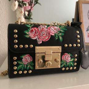 Smuk taske med blomsterdetaljer. Brugt få gange.   Kan sendes billigt med DAO for 38kr på køber regning