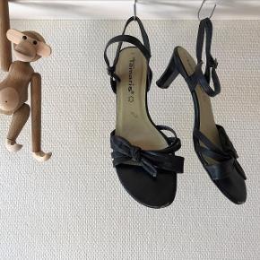 Tamaris sorte sandaler. Sælges for 50 kr. + 35 kr. dao porto. (Jeg har også et par i beige til salg på min profil, se særskilt annonce). Pris for begge par i samlet handel 135 kr. inkl. dao porto. Overdel i skind. Slingback strop så sandalen sidder perfekt på foden. Stødabsorberende mellemsål. Hælhøjde ca. 6 cm. Ikke brugt meget, men har fået nogle få skrammer, der er stadig mange timer i dem, og hælene er også ok. Nypris 700 kr. pr. stk. Jeg rydder op og sælger billigt.