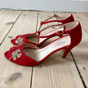Flotte sandaler i rød ruskind med firkløver i guldglimmer og t-rem. Aldrig brugt!  Købt hos Patricia Blanchet i Paris.  Hælhøjde ca. 7 cm.  Æske medfølger.  Bytter ikke, men bud er velkomne.