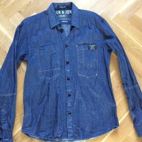Skjorte brugt en enkelt gang og vasket tilsvarende. Trænger højest til et strygejern. Skulder og ned 74 cm. Brystvidde 53*2 cm Indv arm 55 cm