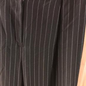 Sorte slacks med smalle hvide striber ☺️   Sender med DAO på købers regning og ellers kan den hentes i Roskilde, Rødovre Centrum eller på Teglholmen efter aftale