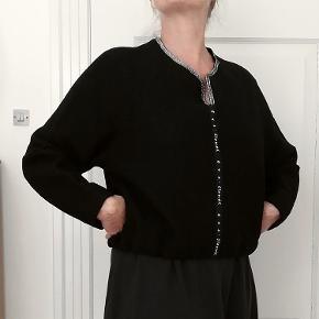 Bytter ikke. Eksklusiv porto Varetype: Trøje/Sweater. Farve: Sort med sølv nister. Købspris: 1.800 kr. Lækker trøje til at tage over hovedet fra Eva & Claudia, str. L. Bånd forneden, der kan reguleres. Størrelsesguide str. L: Bryst mål 95 cm Talje mål 75 cm Længde fra nakke og ned 52 cm. For og bag stykke måle ved bryst linjen, 120 cm. Fast stof i uld: 100% Uld Modellen på billederne er en str. 40 med et bryst mål 92 cm, talje mål 76 cm. Brugt, fremstår i pæn stand.   Trøjen kommer fra et ikke ryger hjem.  Hænger i dragtpose.