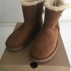 Helt nye UGG støvler i str.38 / brun ruskind med lammefor. Fin lille sløjfe bagpå. Skaftet måler 17 cm incl. sål.  Aldrig brugt.