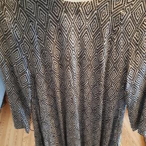 Flot langærmet kjole med sort/hvid mønster. Størrelsen er 34. Kjolen har en fin detalje bag på ved taljen, hvor der er samlet en masse folder. Den er aldrig brugt