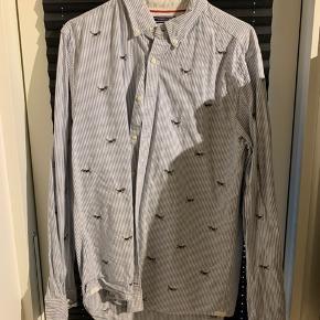 Tommy Hilfiger skjorte i Medium med broderede beagles på. Da en af de stakkels hunde fik lidt for længe med strygejernet (se sidste billede), sælges den billigt.