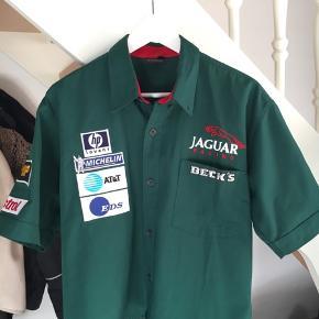 Skjorten er et vintage fund og er et officielt merchandise fra Jaguar. Den er en utrolig god stand, uden nogle form for skrammer. Alle sponsor mærker er brodiert   Skjorten var oprigtigt en str. XL men har været til en skrædder for at passe en str. S