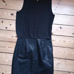 Sort kjole fra ONLY. Str. 34 Aldrig brugt.  Underskørtet er mat PU Slids og guldknap i ryggen Der er foer i skørtet Total længde: 92 cm fra skulder til bund. Kan afhentes i Esbjerg. Sender gerne- køber afholder fragt og risiko