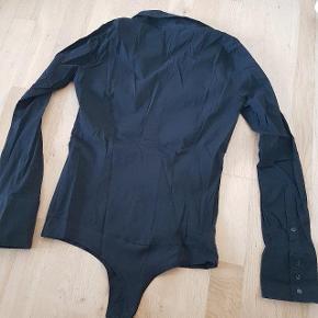 Sort stretch body i skjortemodel fra Vero Moda. Str. L.  Aldrig brugt.  Kan afhentes i Rødovre eller sendes på købers regning med DAO.