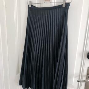 Flot midi plisseret nederdel, der passer en S-M  Sort/mørkegråt tungt materiale med en smule shine