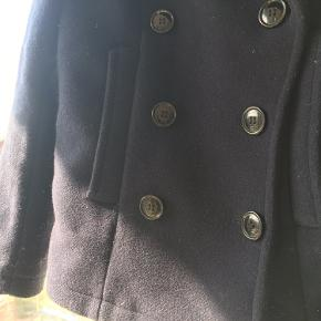 Kort mørkeblå jakke i filtet uldblanding med dobbelt række knapper.
