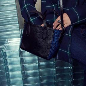 """Varetype: Smuk lædertaske med rem Størrelse: 20x19 Farve: sort blå Oprindelig købspris: 1900 kr.  Sælger denne smukke """"mini Morlett"""" taske fra Leowulff, da jeg ikke har taget den i brug endnu. Den er i ægte læder, og har super cool blå detaljer på siden  Bredde 20 cm Højde 19 cm Dybde 11 cm  Hentes på frederiksberg eller sendes mod betaling"""