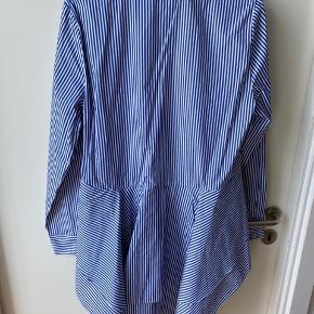 Skjorten er længere bagpå og kort foran med peplum effekt.