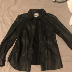 Super lækker skind skjorte i sort i det blødeste skind - figursyet.  Nypris 2500 kr og brugt 2 gange. Bytter ikke. Mærket - Noize