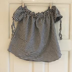 Fin lille top fra H&M aldrig brugt. Elastik- rib ved halsudskæring og små ærmer med binde-sløjfer på hver ærmekant. Lille i størrelsen.