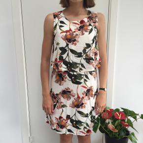 Hvid, blomstret kjole fra ONLY. Str. 38, men fitter også en 40. Knappefunktion i nakken.